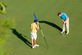 Two golfers on putting green during a round of golf