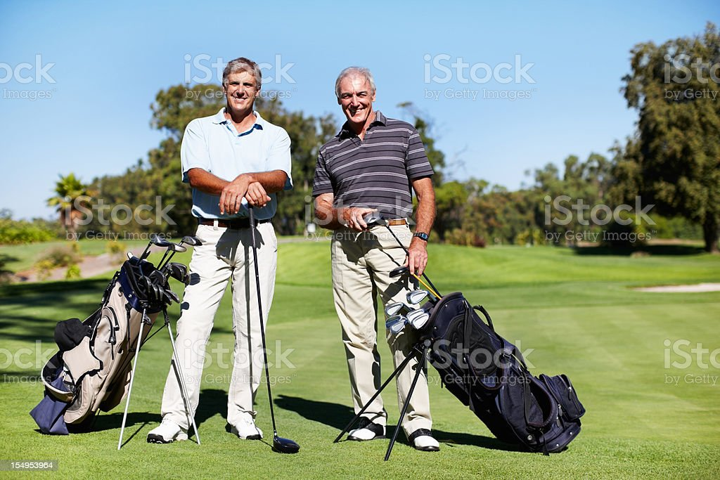 Golfers standing with golf sticks on course stock photo