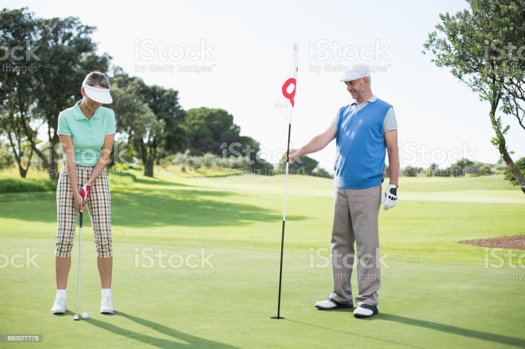 Golfing couple at the eighteenth hole on the golf course stock photo