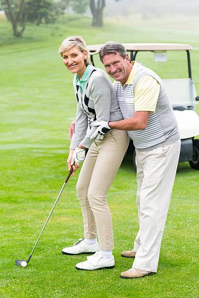 golfen paar putting ball zusammen, lächelt in die kamera. - sanft und sorgfältig stock-fotos und bilder