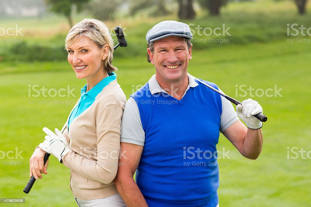 Golfing couple smiling at camera on the putting green stock photo
