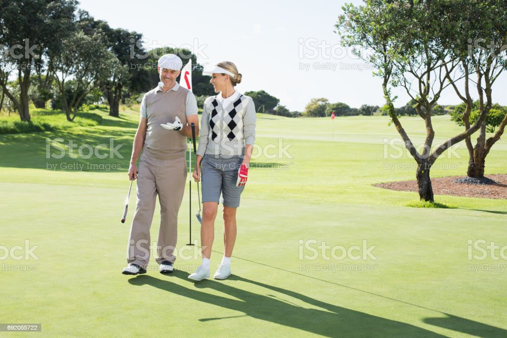 Golfing couple smiling at each other on the putting green stock photo