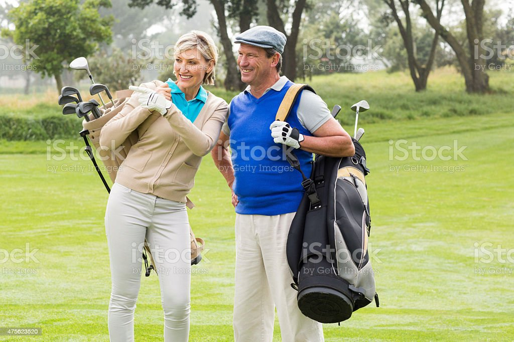 Golfing couple walking on the putting green stock photo
