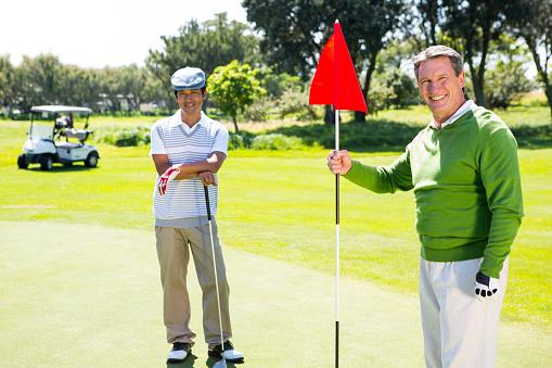 Golfing friends smiling at camera