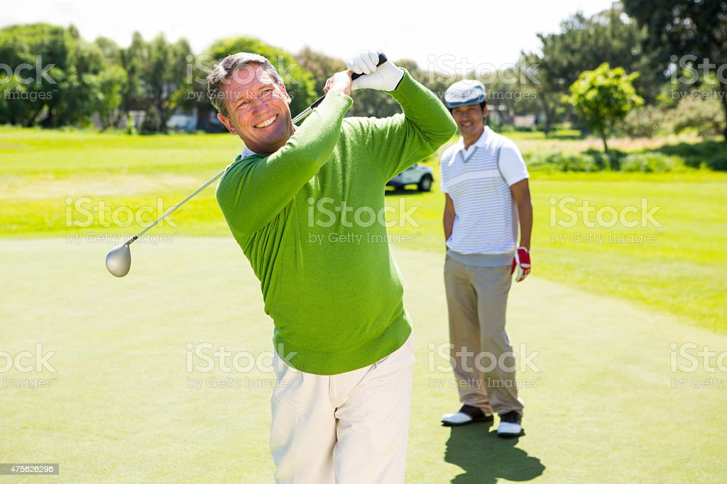 Golfing friends teeing off stock photo