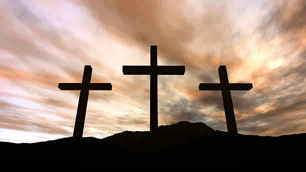 Golgotha - silhouette of three crosses on a hill with clouds stock photo