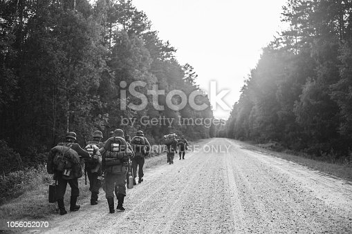 1143756392 istock photo Gomel, Belarus. German Infantry Soldier In World War II Marching Walking Along Forest Road In Summer Evening. Photo In Black And White Colors. 1056052070