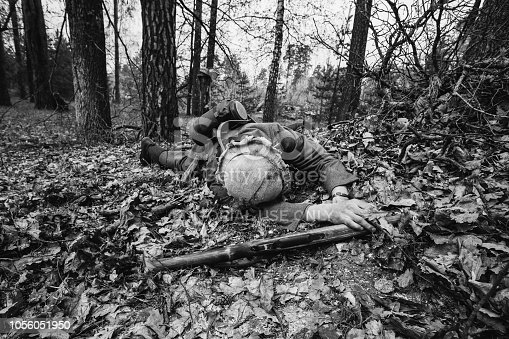 istock Gomel, Belarus. German Wehrmacht Infantry Soldier In World War II Soldier Lying Dead On Battlefield At Historical Reconstruction In Autumn Forest. Photo In Black And White Colors. 1056051950