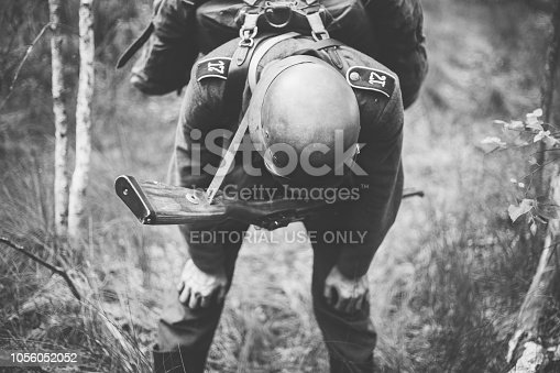 1061204700 istock photo Gomel, Belarus. German Wehrmacht Infantry Soldier In World War II Trying To Catch His Breath At Rest In Forest In Summer Day. Photo In Black And White Colors. 1056052052