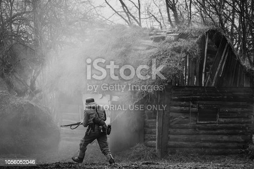 istock Gomel, Belarus. German Wehrmacht Infantry Soldier In WW II Running On Battlefield Near Burning Wooden House. Photo In Black And White Colors. 1056052046