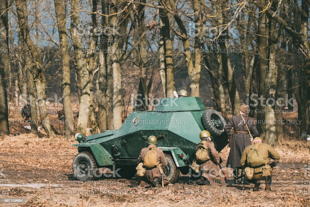 Gomel, Belarus. Group Of Reenactors Dressed As Russian Soviet Red Army Soldiers Of World War II Go On Offensive Under Cover Of Armored Soviet Scout Car Ba-64. Historical Reenactment In Forest stock photo