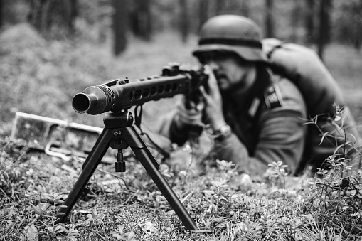 istock Gomel, Belarus. Hidden German Wehrmacht Soldier Aiming A Machine Gun At Enemy From Trench In Forest. Photo In Black And White Colors 1056052040