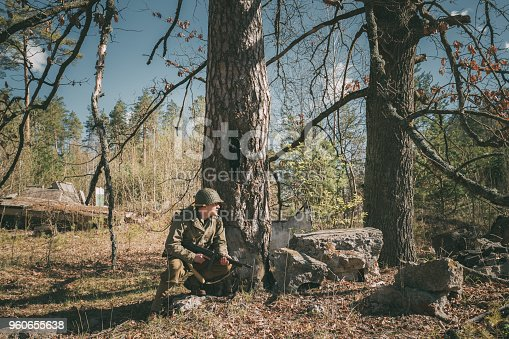 istock Gomel, Belarus. Re-enactor Dressed As Soldier Of United States Of America Infantry Of World War II Hidden Sitting With Thompson Sub-machine Gun In Forest Ambush At Historical Reenactment 960655638
