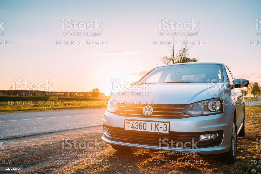 Gomel, Belarus. VW Volkswagen Polo Vento Sedan Car Parking Near Asphalt Country Road In Sunny Sunset. Sunlight Above Road In Sunrise. Gomel, Belarus - May 16, 2017: VW Volkswagen Polo Vento Sedan Car Parking Near Asphalt Country Road In Sunny Sunset. Sunlight Above Road In Sunrise. Belarus Stock Photo