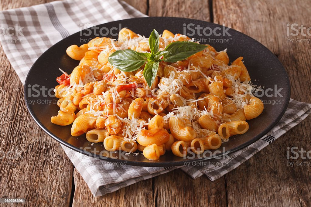 gomiti pasta with tomatoes, beans and parmesan on a plate stock photo