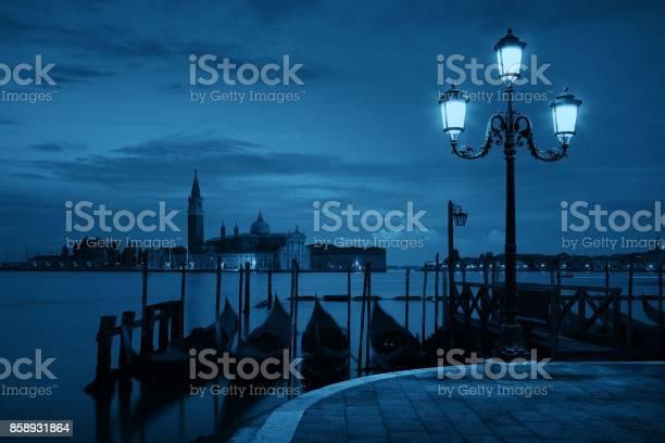 Gondola park in water and San Giorgio Maggiore island in early morning in Venice, Italy.