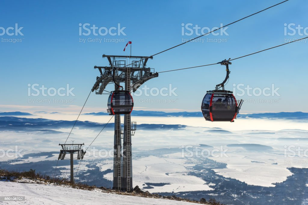 Gondola lift. Cabin of ski-lift in the ski resort in the early morning at dawn with mountain peak in the distance. Winter snowboard and skiing concept stock photo