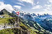 Wengen, Switzerland - August 14, 2019: Swiss alps, Aerial cableway station on top of the Männlichen between Wengen, Lauterbrunnental and Grindelwald. A swiss flag and some tourists on a viewing platform.