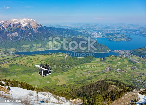 Mt. Stanserhorn, Switzerland - May 7, 2016: people in a gondola of the Stanserhorn Cabrio aerial cable car heading downwards from the station on the top of the mountain, summit of Mt. Pilatus in the background. The Stanserhorn Cabrio is the world's first double deck open top aerial cable car, it carries 60 passengers per cabin with room for 30 on the open deck. The Stanserhorn is a mountain located in the Swiss canton of Nidwalden, near to its border with the canton of Obwalden.