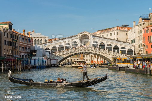 View of a gondola with tourist in the Grand Canal near the Rialto Bridge at Venice, Italy. The Grand Canal is an ancient waterway that goes from the Saint Mark Basin to a lagoon near the Santa Lucia rail station and is lined with buildings constructed from the 13th to the 18th centuries by wealthy Venetian families. The Rialto bridge is considered the most beautiful and famous of the four bridges that cross the Grand Canal. The gondola tour is a preferred attraction for the tourist at Venice.