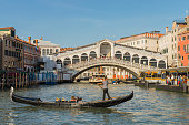 View of a gondola with tourist in the Grand Canal near the Rialto Bridge at Venice, Italy. The Grand Canal is an ancient waterway that goes from the Saint Mark Basin to a lagoon near the Santa Lucia rail station and is lined with buildings constructed from the 13th to the 18th centuries by wealthy Venetian families.\nThe Rialto bridge is considered the most beautiful and famous of the four bridges that cross the Grand Canal. The gondola tour is a preferred attraction for the tourist at Venice.
