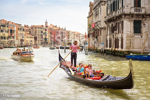Venice, Italy - May 19, 2017: Gondola with people sails on Grand Canal in sunny Venice. Gondola is a most attractive tourist transport of Venice. Romantic travel in Venice in summer.