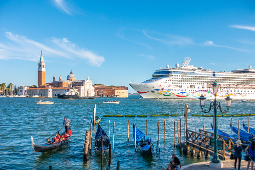 Venice, Italy – August 13, 2017:  Gondola full of people with San Giorgio Maggiore island on the background and an ocean cruiser
