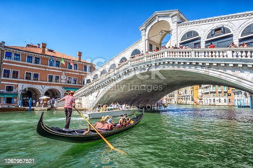 Venice, Italy – August 15, 2017:  Gondola with tourists on Gran Canal with Rialto Bridge, Venice