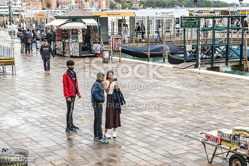 This is a wide angle image of the Gondola stations at San Marco Square in Venice, Italy with a boarding station and tourists in the gondolas and taking photos on the canal side.