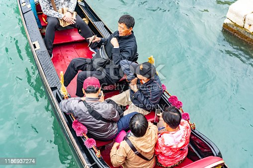 A Gondola with tourists on board approaching the gondola stations at San Marco Square in Venice, Italy.