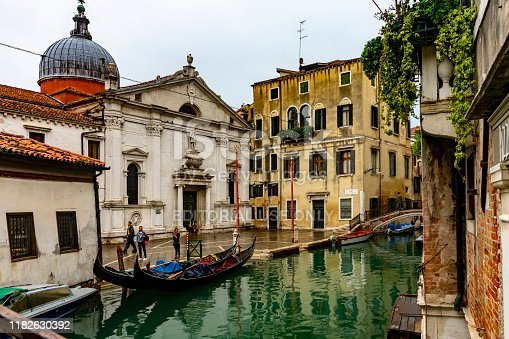 This is a wide angle image of a gondola station at Santa Maria Formosa church in Venice, Italy. There are tourists and the church in the background and gondolas moored at the side of the canal.