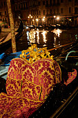 Details of a gondola seating decorated with soft pillow and wood carved statues. Venezia. Italy.