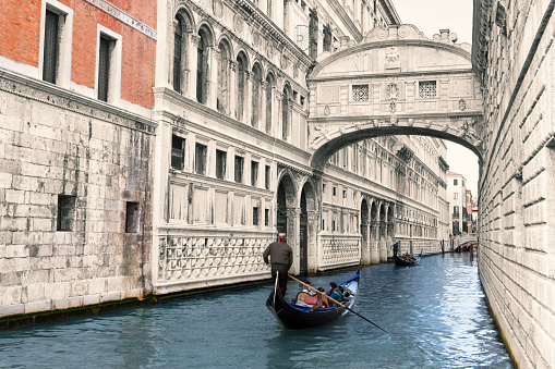 Gondolas is passing over Bridge of Sighs in Venice, Italy
