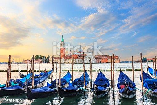 Gondolas moored at the pier in Grand Canal with San Giorgio Maggiore in the background, Venice, Italy.