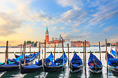 Gondolas moored at the pier in Grand Canal with San Giorgio Maggiore in the background, Venice, Italy.