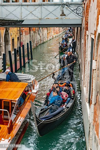 Venice Greci canal  with Gondolas and tourists near the San Zaccharia water bus stop. The gondoliers are in traditional dress and are steering the gondolas past other craft. Some are pushing off from the wall.