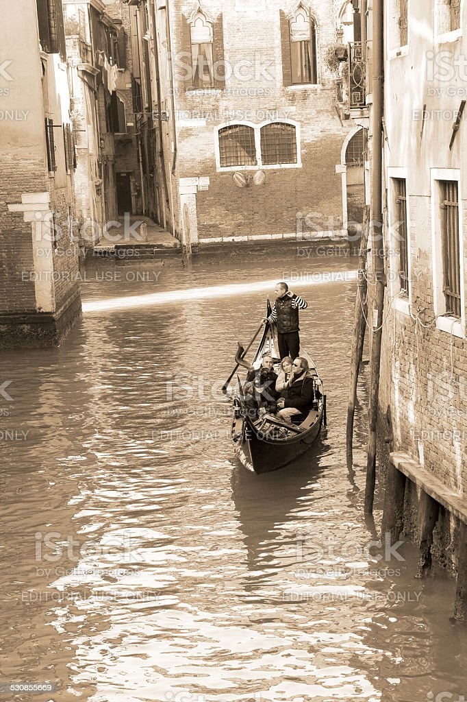 Gondolier carrying tourists in Venice, sepia tone stock photo