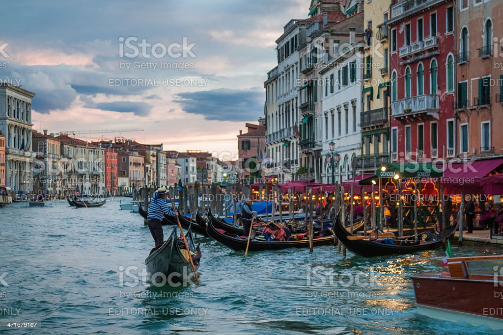 Gondolier floating near restaurants in Venice royalty-free stock photo
