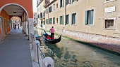 Venice, Italy - May 23, 2011: Gondolier in Rio del Magazen, one of Venice canals. Some tourists on the canal side, under a porch and crossing a bridge