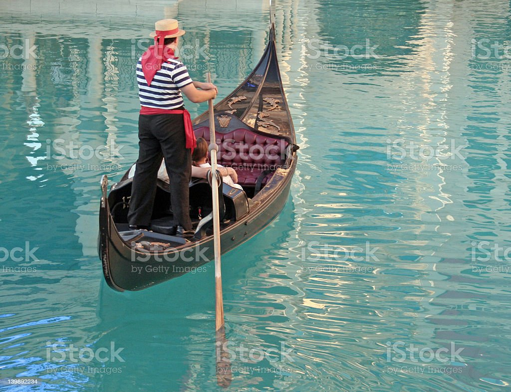 A gondolier on a gondola in the water royalty-free stock photo
