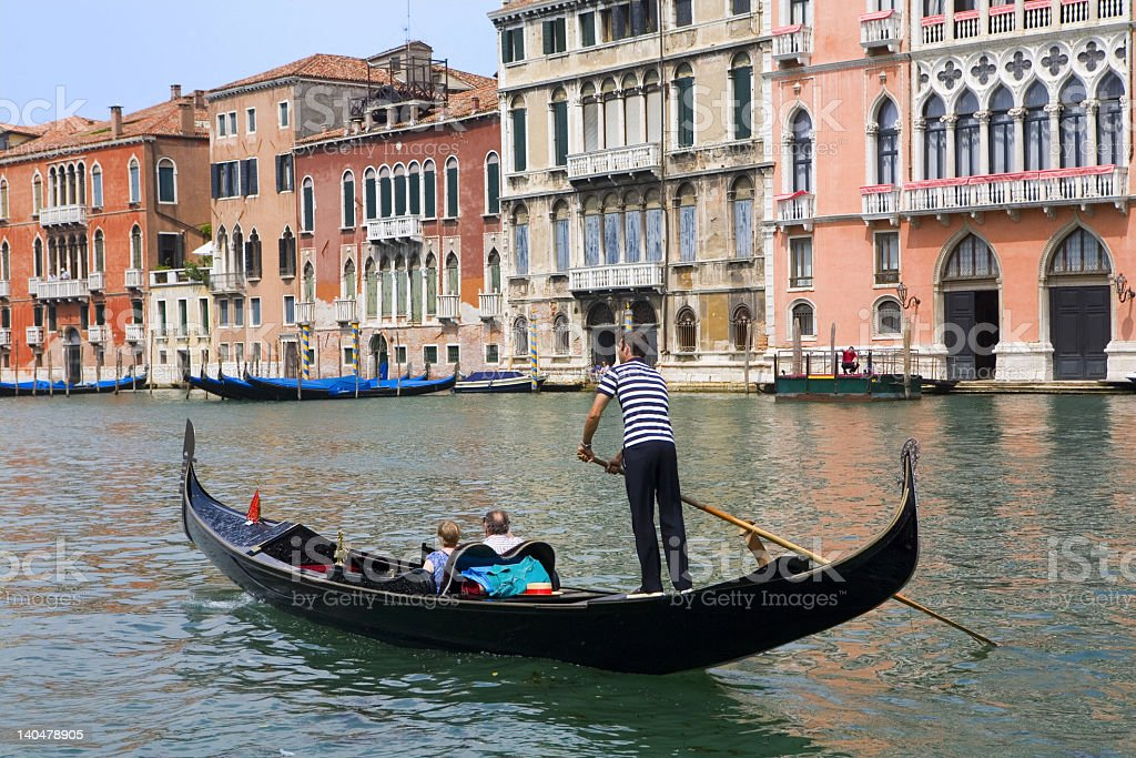 Gondolier on a gondola with passengers on the river royalty-free stock photo