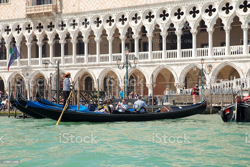 Gondolier wearing traditional dress in the gondola and sail stock photo