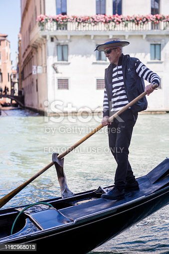 Venice, Italy - May 6 2019: Gondolier with classical uniform and hat, rowing on Canal Grande