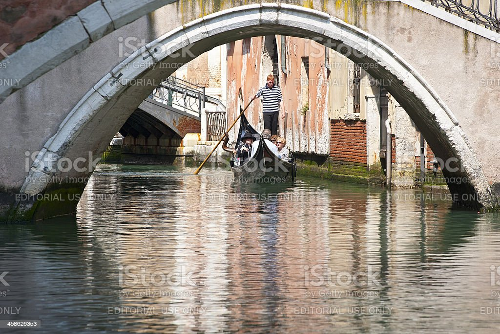 Gondoliere with tourists in a canal, Venice, Italy royalty-free stock photo