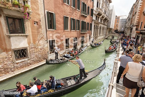 Venice, Italy, Sept 13, 2015: Group of tourists sitting in the gondola with the gondolier, typical Venetian row boat, other tourists stroll along the canal. Sightseeing tour along the narrow canals of the famous city. The gondola is a traditional, flat-bottomed Venetian rowing boat, well suited to the conditions of the Venetian lagoon. It is similar to a canoe, except it is narrower. It is propelled by a gondolier, who uses a rowing oar, which is not fastened to the hull, in a sculling manner and acts as the rudder.