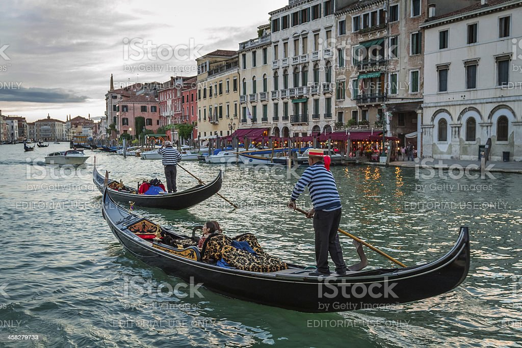 Gondoliers sailing with tourists on the Grand Canal at sunset royalty-free stock photo