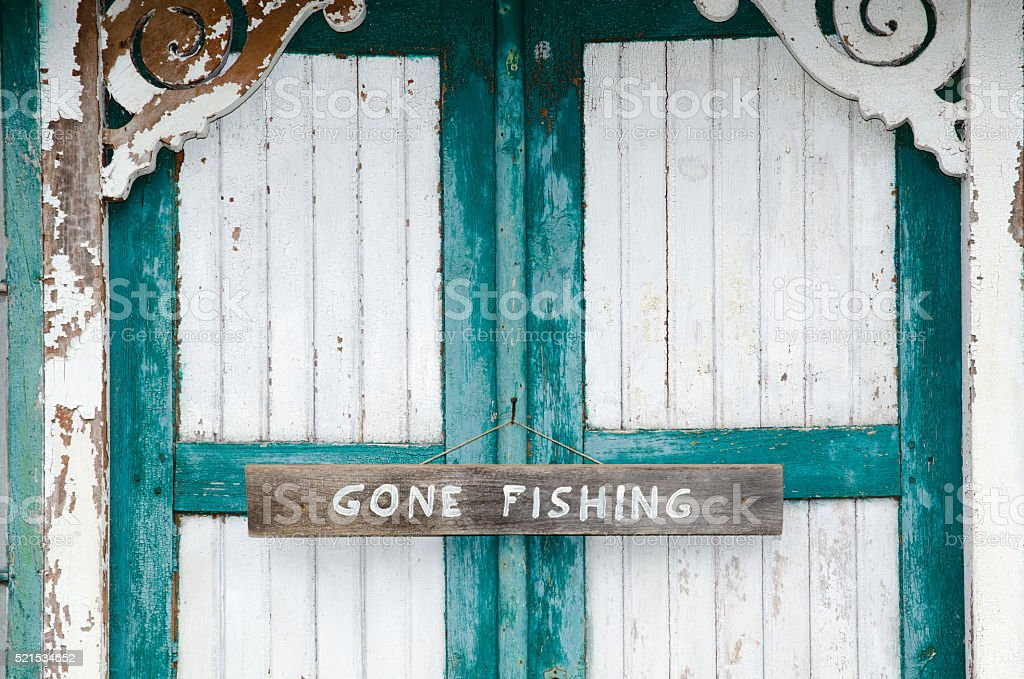 Gone fishing sign at weathered doors stock photo