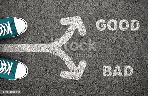 Good Versus Bad Written On The Road. Man standing on crossroad with arrows showing different directions.