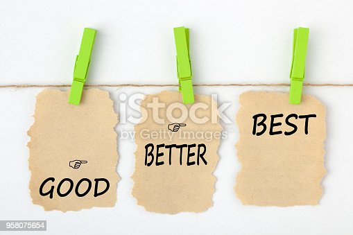 GOOD BETTER BEST writen on old torn paper with clip hanging on white background. Business concept words.