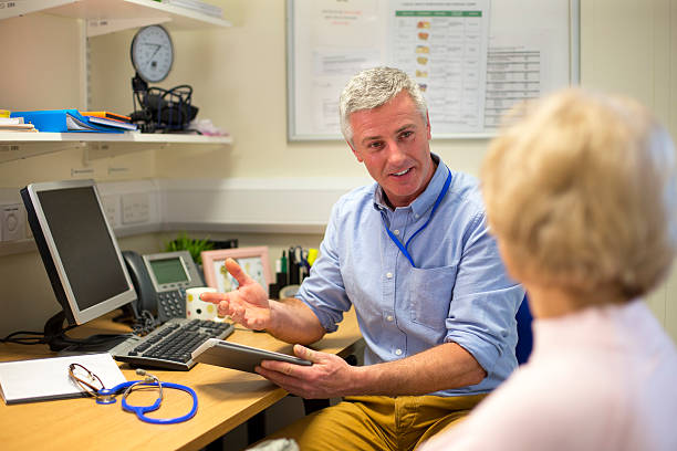 Good Bill of Health A male doctor sits face to face with an elderly woman. They are in the doctors office . The focus is on the doctor who sits at his desk holding a digital tablet and smiling at the woman. The woman face cannot be seen. general practitioner stock pictures, royalty-free photos & images